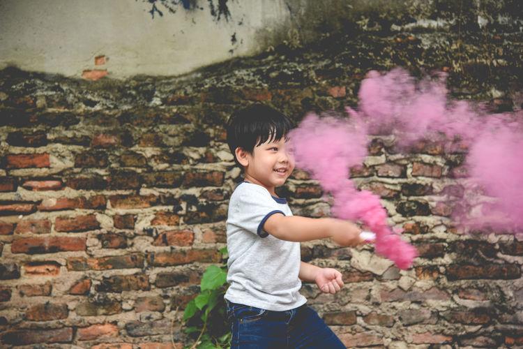 Portrait of happy boy with smoke bomb