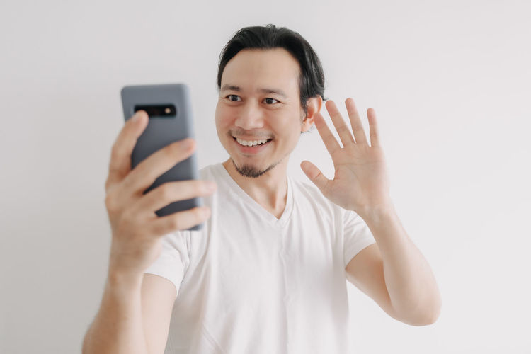 Portrait of smiling man using smart phone against white background