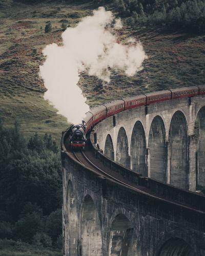 Train on bridge against mountain