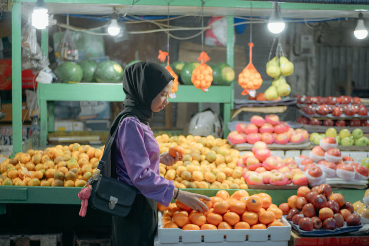 Rear view of fruits for sale at market stall