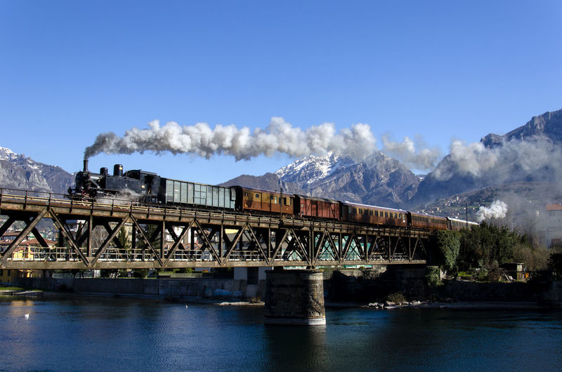 Smoke emitting from train on bridge over river in city