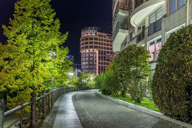 Road amidst trees and buildings in city