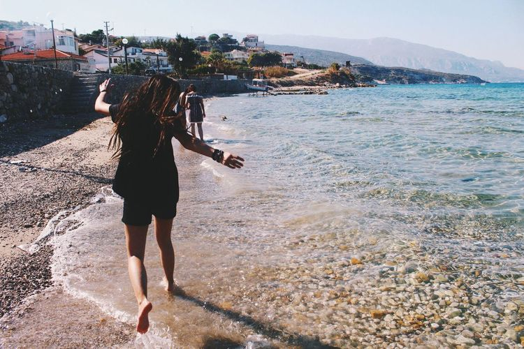 Jump Sea Water Beach Full Length Vacations Rear View Leisure Activity Tranquil Scene Lifestyles Incidental People Person Shore Scenics Casual Clothing Young Women Long Hair Tranquility Tourist