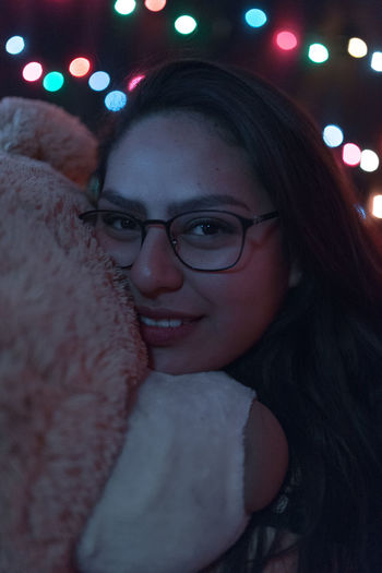 Close-up portrait of young woman with teddy bear against illuminated lights
