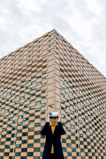 Low angle view of man standing against building against sky