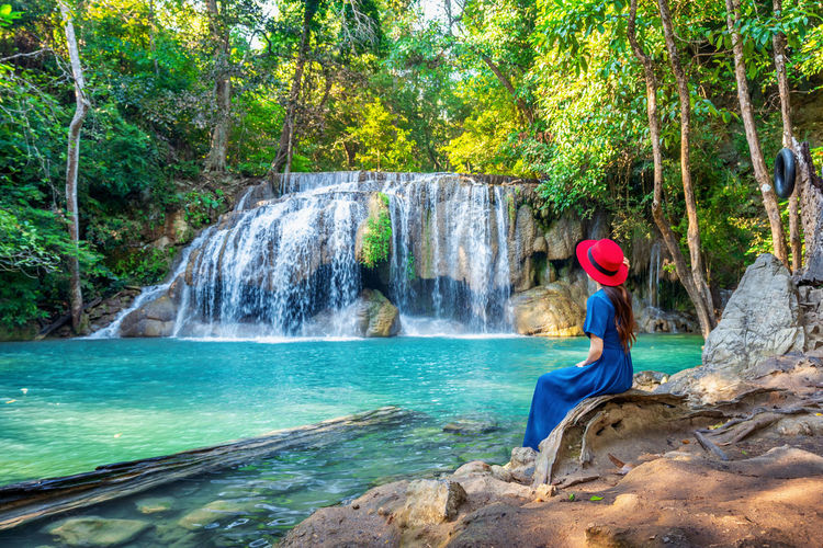 Woman sitting at Erawan waterfall in Thailand. Beautiful waterfall with emerald pool in nature. Water Tree Waterfall Plant Forest Land One Person Motion Nature Beauty In Nature Rock - Object Scenics - Nature Rock Young Adult Solid Travel Destinations Women Day Flowing Water Outdoors Rainforest WoodLand