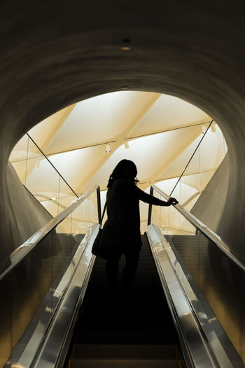 Woman standing on escalator against patterned ceiling