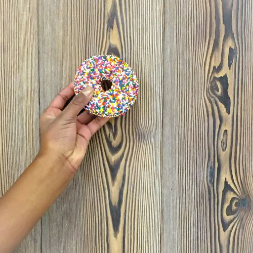 Cropped Image Of Hand Holding Donut Against Wooden Table