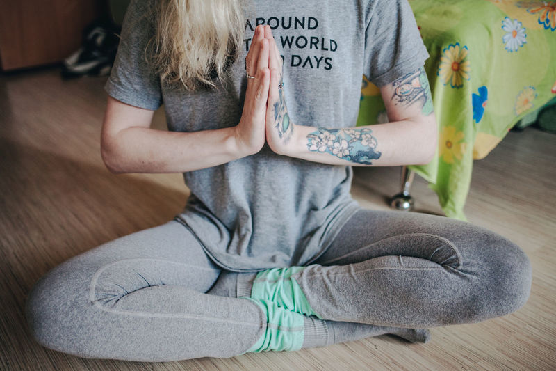 Low Section Of Woman Meditating While Sitting On Floor At Home