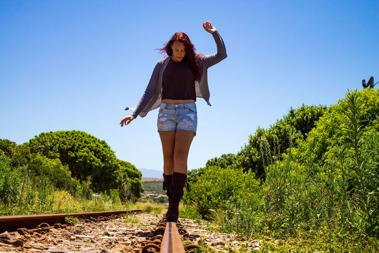 Full length of young woman standing on railroad track against sky