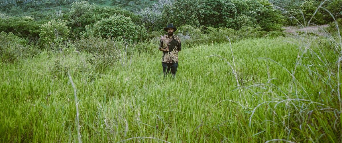 Portrait of man standing amidst plants