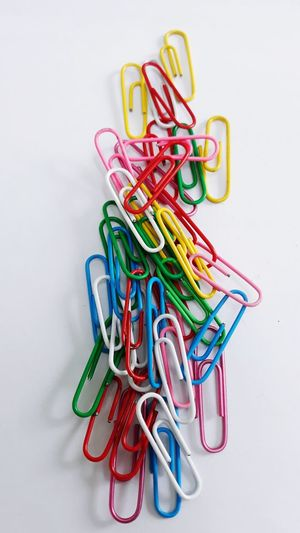 High angle view of colorful paper clips on white background