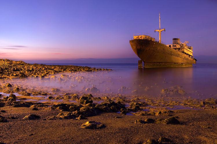 Ship in calm sea against blue sky