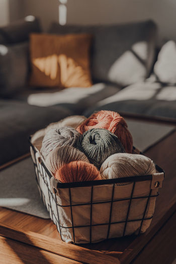 Balls of earth coloured yarn inside a basket on a table inside an apartment.