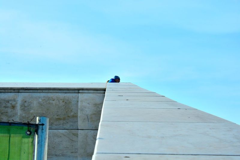 Close-up of man against blue sky