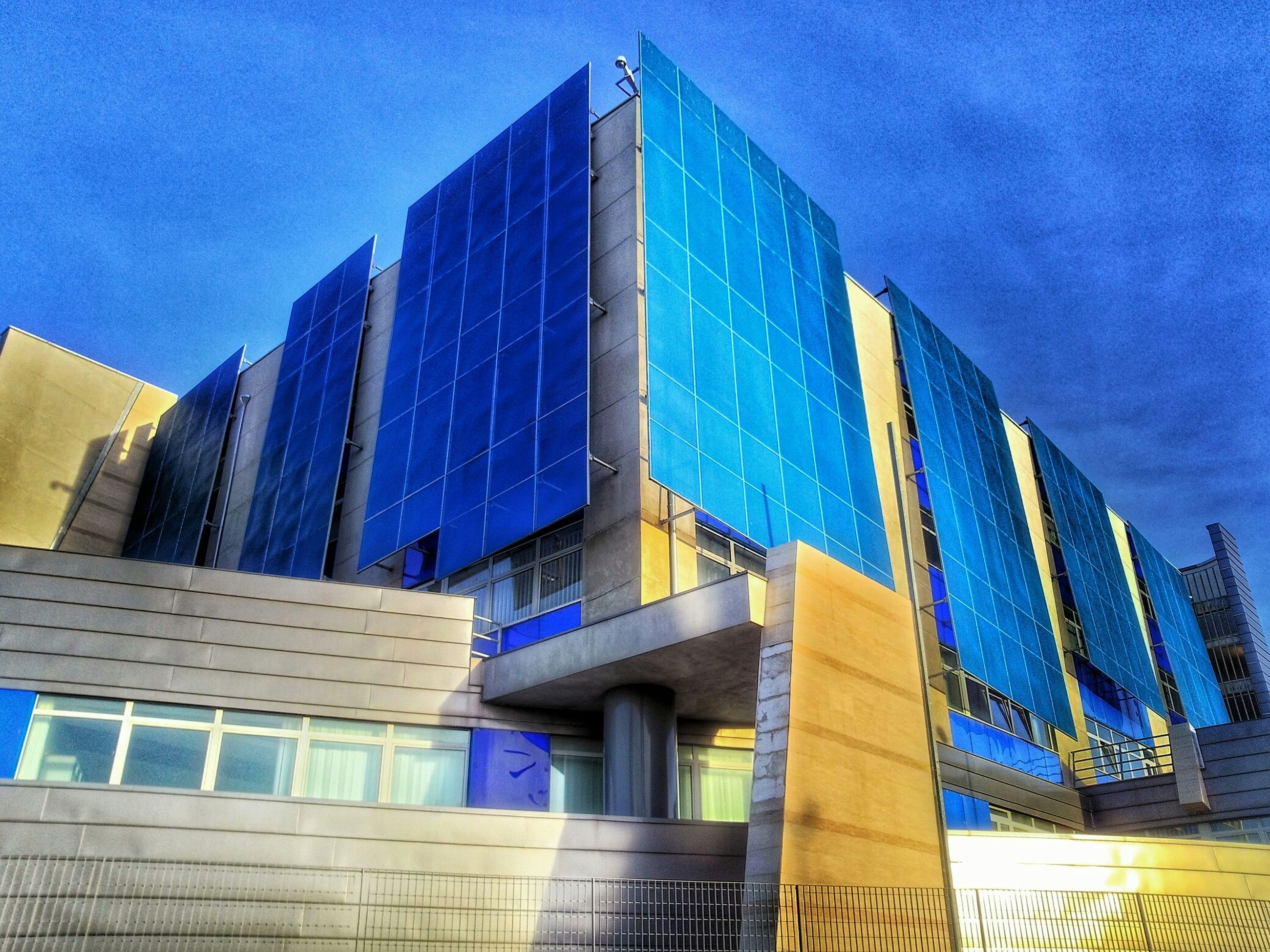 architecture, built structure, building exterior, blue, low angle view, building, modern, city, window, reflection, sky, glass - material, office building, outdoors, sunlight, day, no people, residential structure, residential building, tower