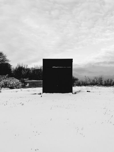 Built structure on snow field against sky