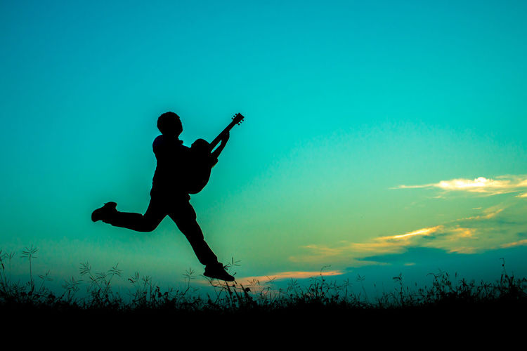 Silhouette Man Jumping While Holding Guitar Against Sky During Sunset