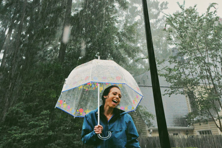 Happy woman holding umbrella during rainfall
