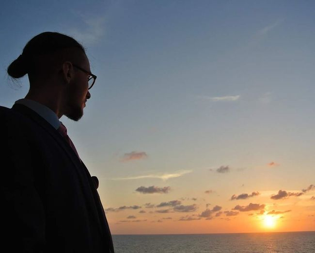 Side view of man looking at sunset over sea against sky