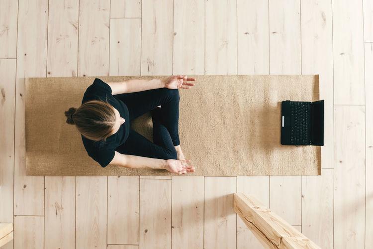 Top view of woman woman practicing yoga indoor.