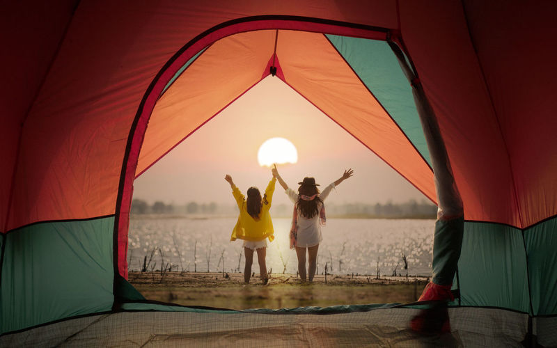 Tent view on window with woman standing and open hand on sunset or sunrise background Tent View Standing Open Hand Sun Sunlight Sunset Sunrise Happy