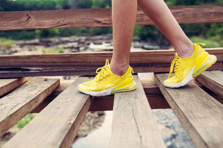 Yellow shoes sport style walking on wooden bridge One Person Human Body Part Body Part Human Leg Wood - Material Low Section Shoe Day Limb Real People Lifestyles Human Limb Women Boardwalk Yellow Outdoors Nature Leisure Activity Human Foot Wood Shose Sport Hiking Walking Bridge - Man Made Structure River Camping Journey Woman Portrait Foot