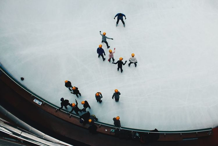 High angle view of people ice-skating on frozen landscape