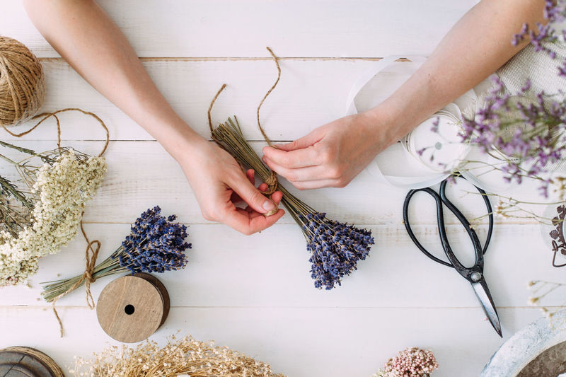 Hands of a florist woman at work. dry compositions of flowers and plants for the interior