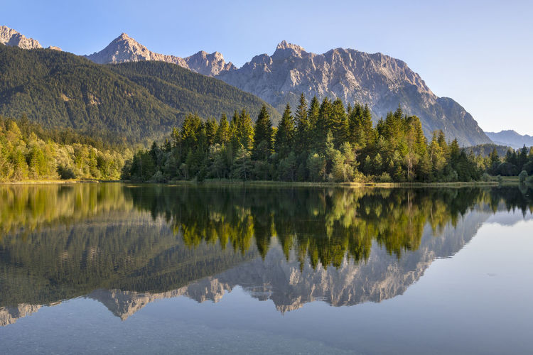 Panoramic landscape at karwendel mountains with reflectuion in river isar