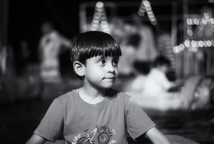 Boy looking away while sitting outdoors