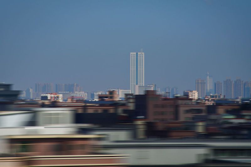Blurred motion of buildings in city against clear sky