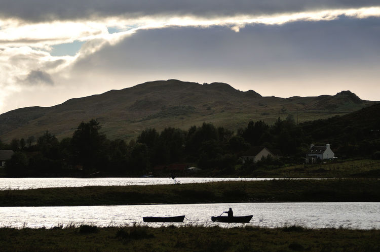 Man rowing his boat to shore on Loch Long - Dornie, Highlands of Scotland Cloud Cloud - Sky Cloudy Highlands Lake Loch  Mountain Non Urban Scene Non-urban Scene Outdoors Rowing Rowing Boat Scotland Scottish Highlands Tranquil Scene Water