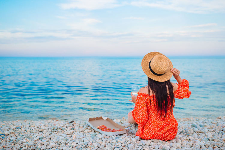 Rear view of woman wearing hat sitting on beach against sky