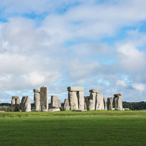 Megalith rocks on grassy field against cloudy sky