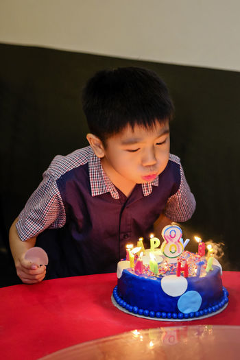 Cute Boy Blowing Birthdays Candles On Cake