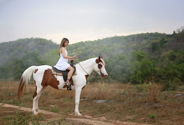Full length of young woman riding horse