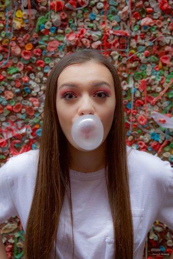 Portrait of woman blowing bubble gum