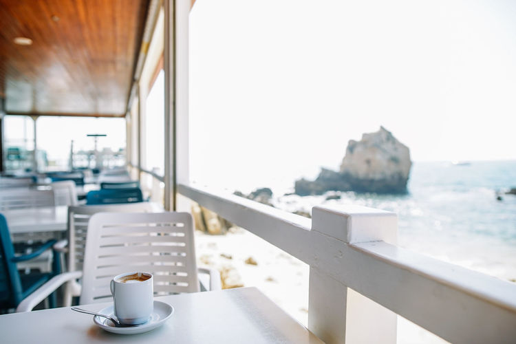 Coffee cup on table by sea