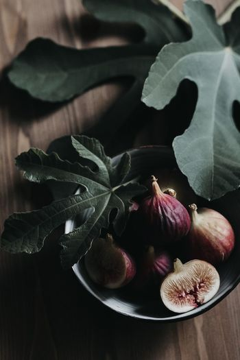 High angle view of fruits and leaves on table