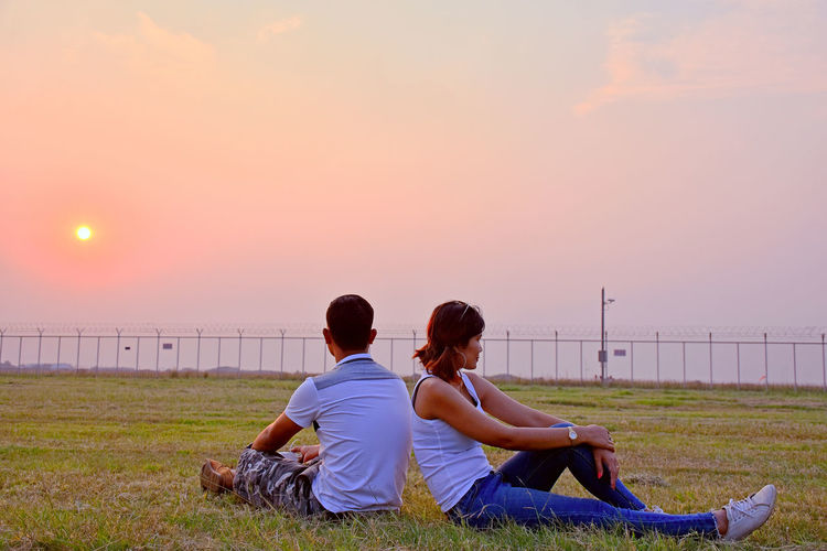 Couple sitting on grassy field against sky during sunset