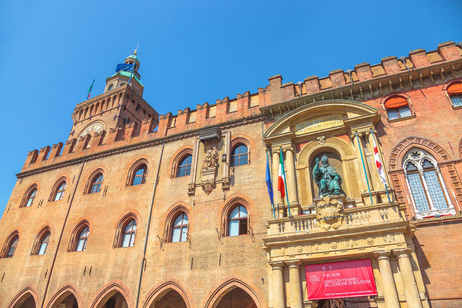 Bologna, Italy - May 28, 2016: Palazzo Re Enzo, historical landmark palace and heart of economic and social activities of the city with many people and the main square called Piazza Maggiore. People walking in via Rizzoli, restricted traffic zone, closed to traffic during the day on Saturday. The Two Towers, icons of Bologna, on background. Tourist train at side of Palazzo dei Banchi in Piazza Maggiore. San Luca Espress is the tourist line which connects the historic center with the Basilica of San Luca. Bologna Bologna, Italy Cathedral Church City Piazza Maggiore San Luca Tourist Asinelli Asinelli Tower  Italian Italy People San Petronio Street Streetphotography Tourism Town Train