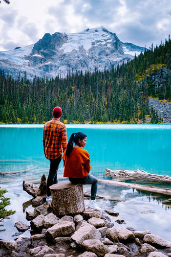 Rear view of couple by lake against mountains and sky