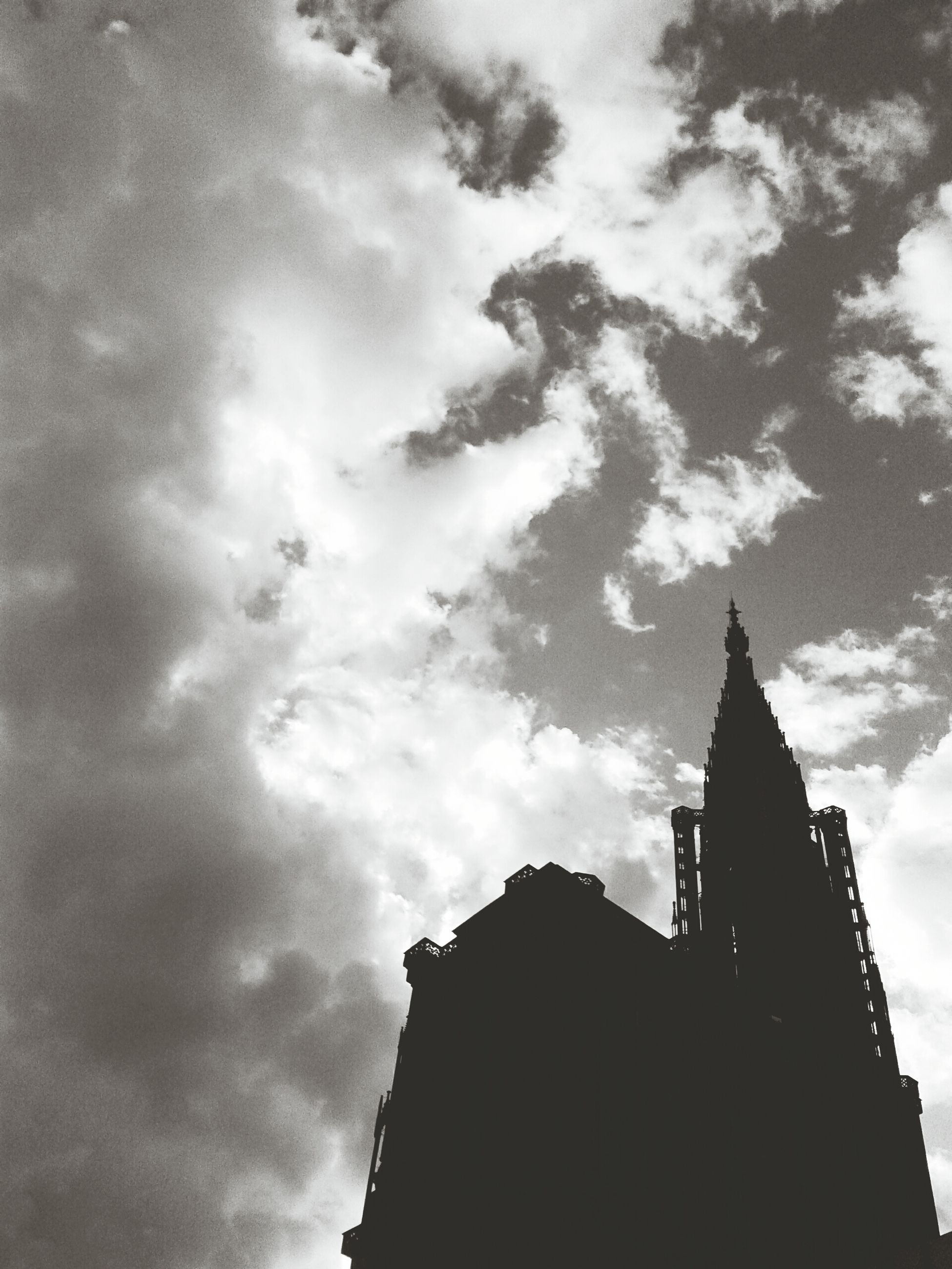 architecture, building exterior, built structure, low angle view, sky, cloud - sky, silhouette, tower, place of worship, religion, city, church, tall - high, cloudy, spirituality, cloud, famous place, travel destinations, outdoors