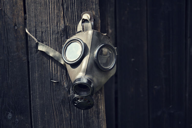 Close-up of gas mask hanging on door