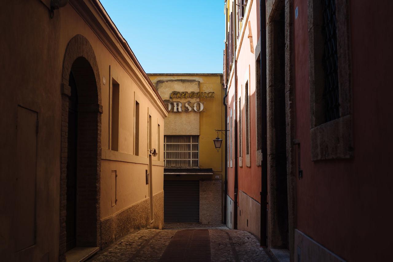 Empty street amidst buildings against clear sky