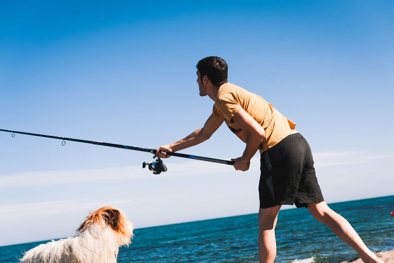 Man with dog by sea against sky