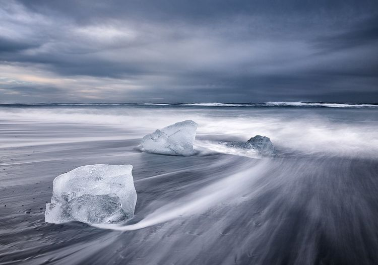 Scenic View Of Icebergs On Beach With Rough Sea Against Cloudy Sky