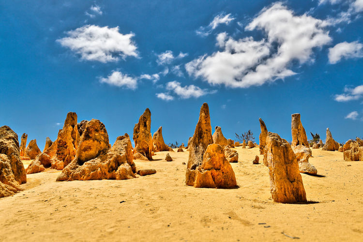 Rock formations on sand blue sky