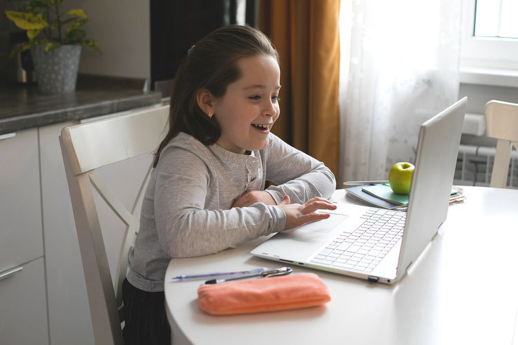 Smiling girl using laptop on table at home